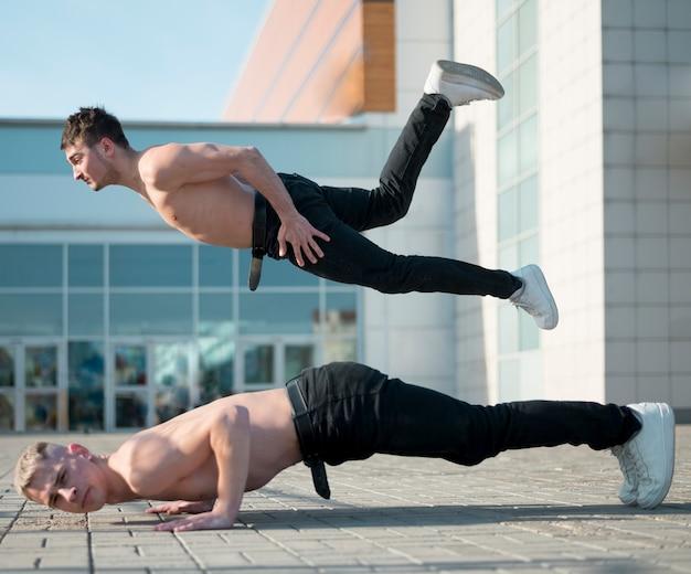 上半身裸のヒップホップのパフォーマーのダンスの側面図