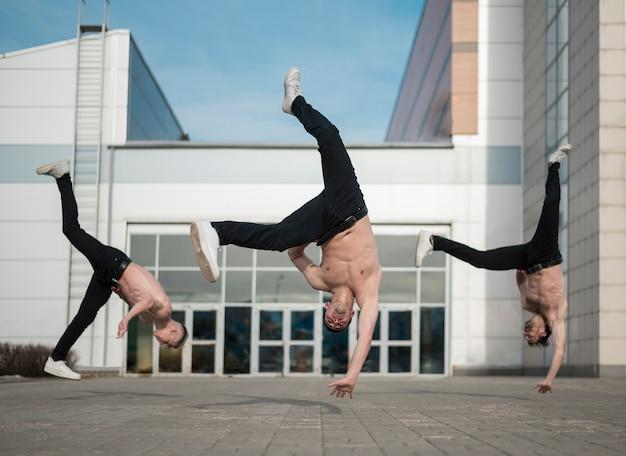 外で練習している上半身裸のヒップホップアーティストの正面図