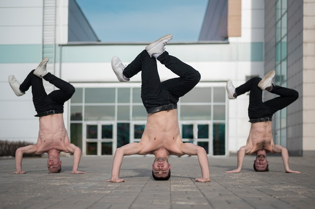 彼らの頭の上に立っている上半身裸の男性ヒップホップアーティスト