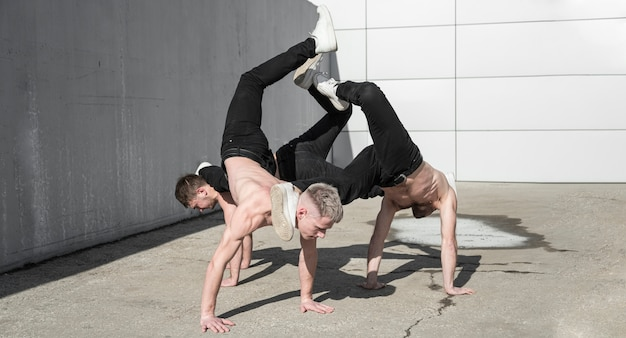 外で一緒に踊る上半身裸のヒップホップアーティスト