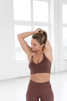 Вид спереди красивой женщины делают упражнения