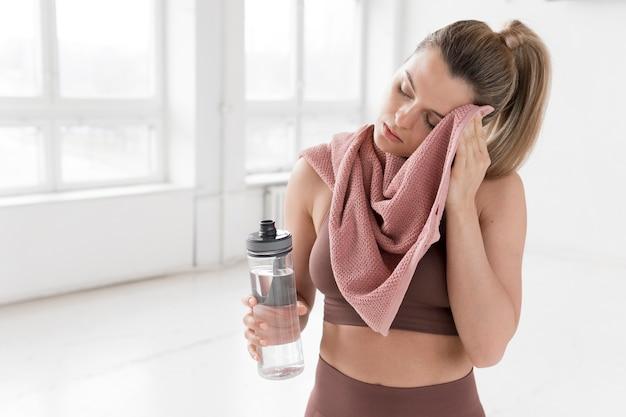タオルと水のボトルを持つ女性の正面図