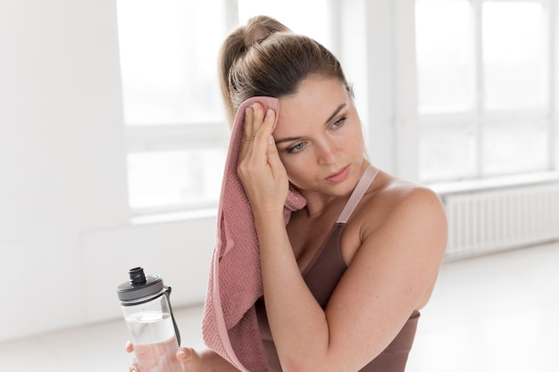 Вид спереди женщины с полотенцем и бутылкой с водой