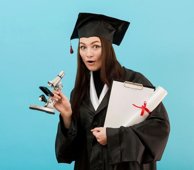 卒業証書と顕微鏡を持つ少女