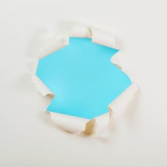 青い背景の破れた紙