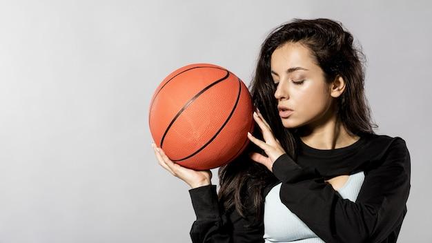 Вид спереди спортивной женщины с баскетбольным мячом