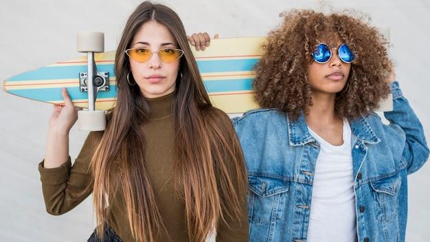 Среднего выстрела девушки держат скейтборд