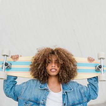 Средний снимок классная девушка со скейтбордом