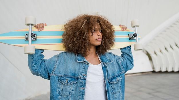 Средний снимок девушка держит скейтборд
