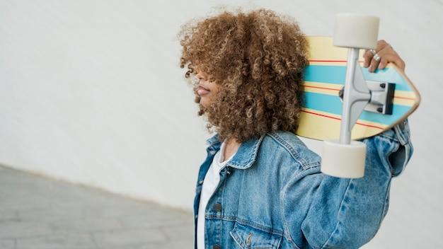 Вид сбоку классная девушка со скейтбордом