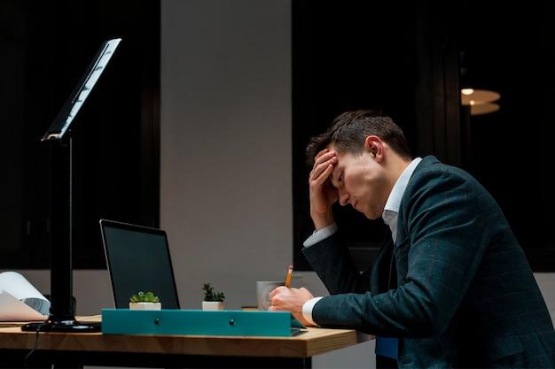 大人の男性が夜に自宅で仕事をした後疲れた