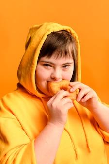 Портрет молодой девушки едят пончик