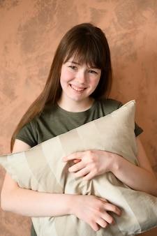 Портрет милой молодой девушки, держащей подушку