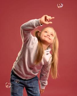 Портрет милая молодая девушка играет с пузырьками