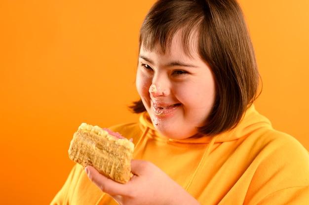 おいしいケーキを食べて幸せな若い女の子
