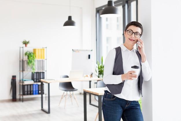 Вид спереди взрослая женщина разговаривает по телефону