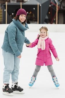 Красивая мама и дочь позирует на улице