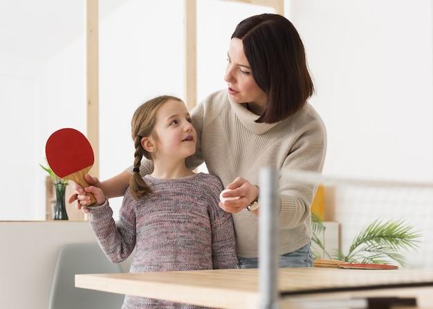 Мать учит дочь пинг-понгу