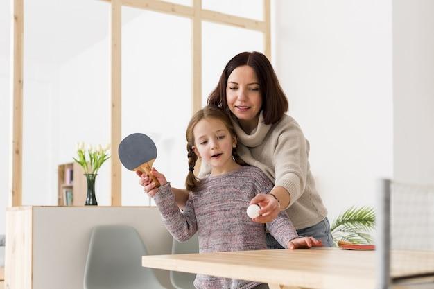 Женщина учит дочь играть в пинг-понг
