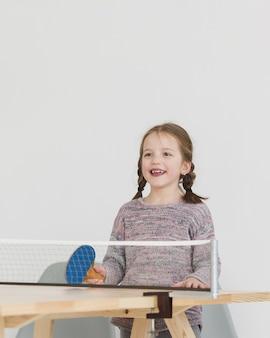 Счастливый ребенок играет в пинг-понг
