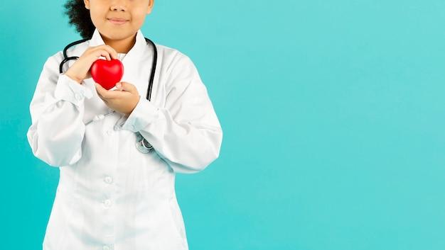 Молодой доктор держит сердце копией пространства