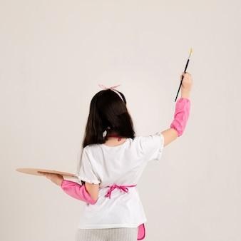 Молодая девушка рисует вид сзади