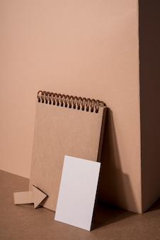 Высокий вид деревянный блокнот и белая корпоративная визитная карточка