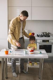 かわいい小さな子供と彼の父親が台所で時間を過ごす