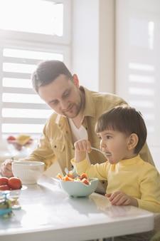 かわいい小さな子供と彼の父親が食べる