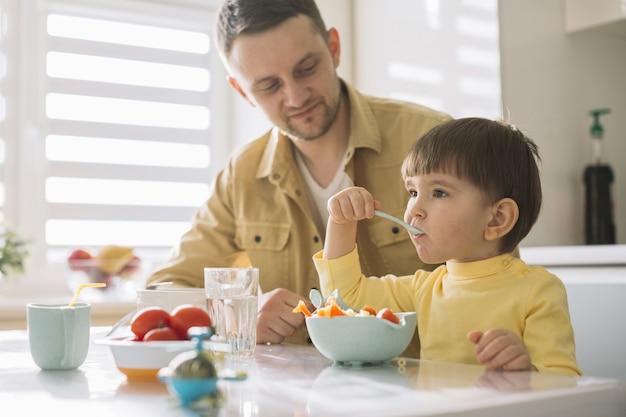 かわいい小さな子供と彼の父親が穀物を食べる