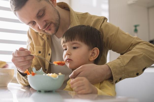 Отец пытается накормить сына
