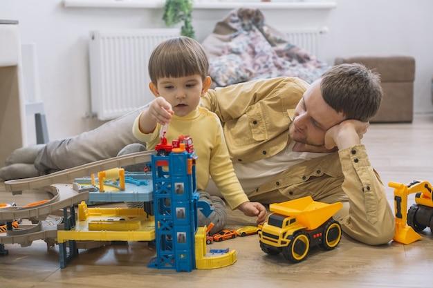 Отец и сын играют с игрушечными машинками