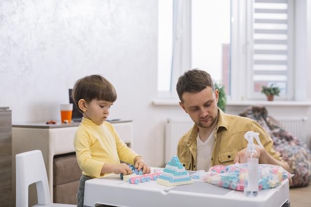 Отец и сын строят игрушки из кусочков лего в помещении