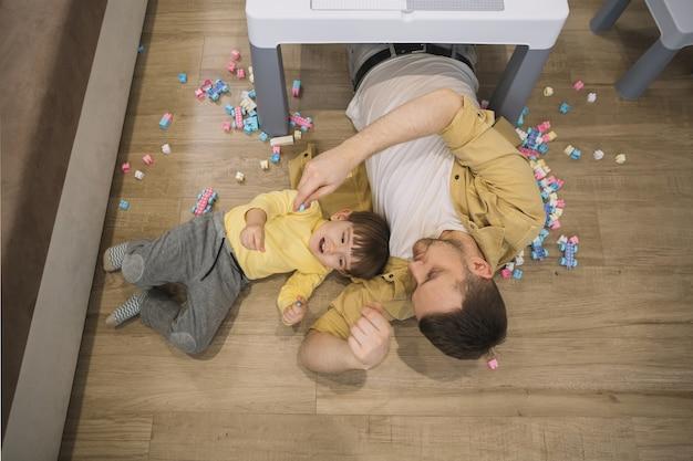 Высокий вид сына и отца, лежащих под столом