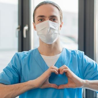 ハートの形を示す医療マスクを持つ看護師男性