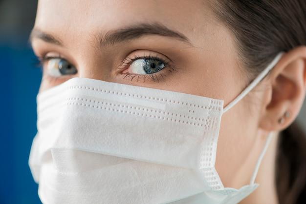 マスクを身に着けているクローズアップの若い看護師