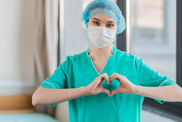 手のハートの形をした看護師