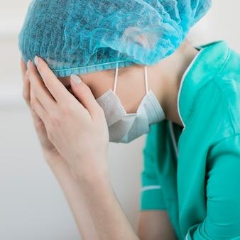 疲れたマスクとクローズアップの看護師