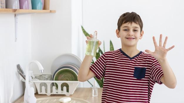 Вид спереди смайлик ребенка, показывая руку, держа жидкое мыло