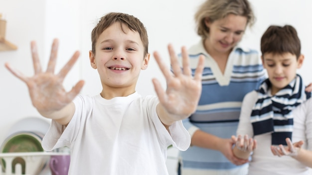 Счастливый ребенок показывает руки во время стирки