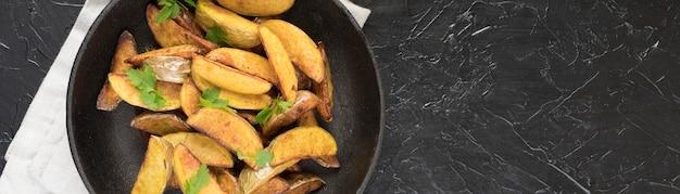 Картофельные дольки в черной тарелке с копией пространства