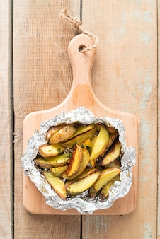 Нарезанный вареный картофель на деревянной доске