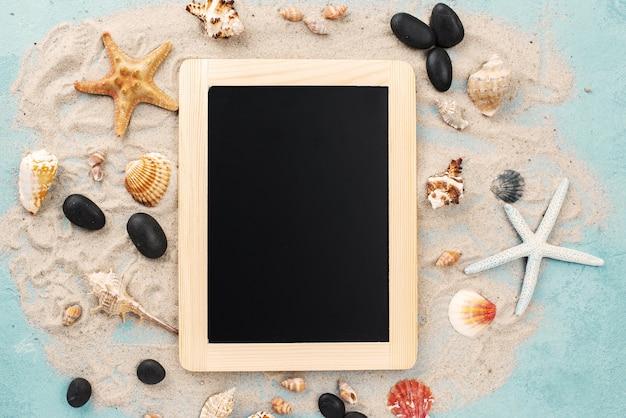貝が付いている砂の上の黒板