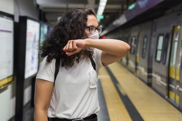 Молодая женщина, кашель во время ношения медицинской маски