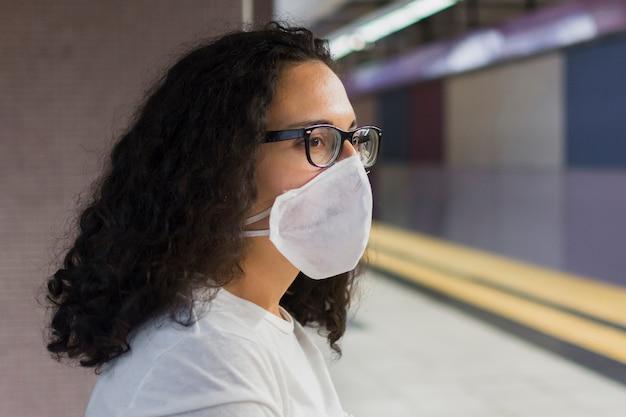 待っている医療マスクを持つ側面図若い女性