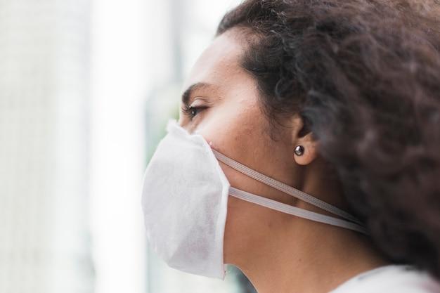 医療マスクのクローズアップで横に若い女性