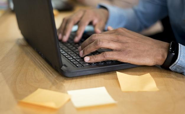 Человек, используя ноутбук для работы в офисе