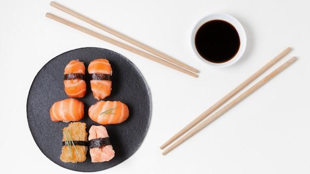 Вид сверху палочки для еды рядом с тарелкой с суши
