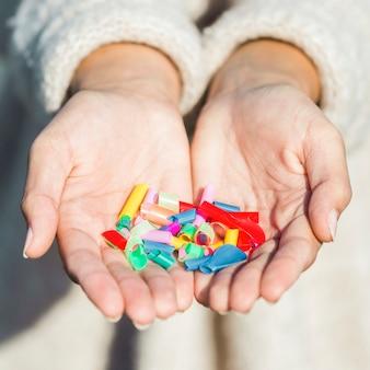 手でプラスチックを持つクローズアップ女性