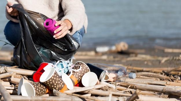 海辺からゴミを拾う女性